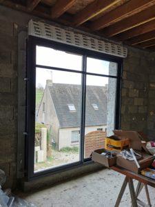 Cette baie vitrée coulissante standard double vitrage en aluminium est de couleur anthracite. On peut y intégrer des volets roulants pour une fermeture plus sécurisée. Le travers posé en haut de la baie vitrée améliore l'aspect esthétique de la pièce.